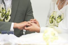 Die Braut trägt einen Ehering auf Bräutigam auf rechtem Ringfinger an ihrem Hochzeitstag lizenzfreies stockbild