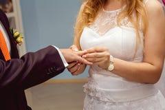 Die Braut tr?gt einen Ring zum Br?utigam stockfotografie