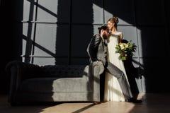 Die Braut umarmt den Bräutigam, der auf dem Arm des Sofas sitzt Sie werden durch hartes Licht vom Fenster beleuchtet Stockbild
