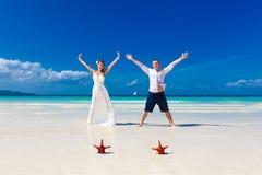Die Braut und Bräutigam, die auf tropischen Strand springen, stützen mit St. mit zwei Rottönen unter Stockfotografie