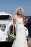 Die Braut und das Hochzeitsauto Lizenzfreie Stockfotos