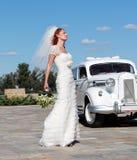 Die Braut und das Hochzeitsauto Lizenzfreie Stockfotografie