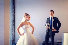 Die Braut und der Bräutigam, die in einem Hotelzimmer mit weißem Innenraum aufwerfen Lizenzfreie Stockfotos