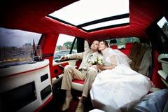 Die Braut und der Bräutigam in einer Hochzeitslimousine Stockfotos