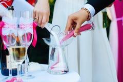 Die Braut und der Bräutigam gießen in einen purpurroten und weißen Sand der Flasche Traditionen der Heirat in Asien Vereinheitlic lizenzfreies stockbild