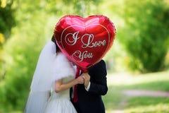 Die Braut und der Bräutigam im Park mit dem roten Ballon mit dem wo Stockbilder