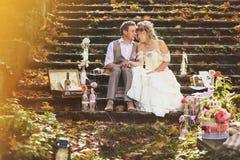 Die Braut und der Bräutigam im Retrostil, der auf Steinschritten am Herbstwald, umgeben durch die Heirat des Dekors umarmt Stockfoto