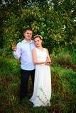 Die Braut und der Bräutigam küssen im Apfelgarten, stehendes u stockfoto