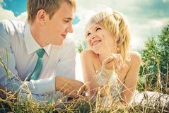 Die Braut und der Bräutigam liegen auf dem Gras Lizenzfreie Stockfotos