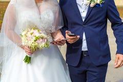 Die Braut und der Bräutigam mit Mobile in der Hand Moderne Hochzeit mit Geräten Stockbilder