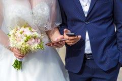 Die Braut und der Bräutigam mit Mobile in der Hand Moderne Hochzeit mit Geräten Lizenzfreie Stockfotos