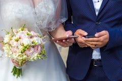 Die Braut und der Bräutigam mit Mobile in der Hand Moderne Hochzeit mit Geräten Lizenzfreies Stockbild