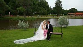 Die Braut und der Bräutigam sitzen auf der Bank des alten Gehöfts Triebkamerakran stock video footage