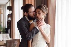 Die Braut und der Bräutigam umarmen sich am Fenster Der Bräutigam streicht die Braut im Gesicht Große Details Lizenzfreie Stockbilder