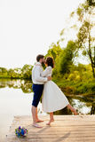 Die Braut und der Bräutigam stehen auf einem hölzernen Pier nahe dem Teich Lizenzfreie Stockfotografie