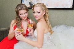 Die Braut und ihre Brautjunfer mit einem Glas Wein Lizenzfreies Stockfoto