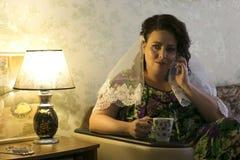 Die Braut wartet auf einen Anruf vom Bräutigam und trinkt Kaffee morgens Stockfotografie