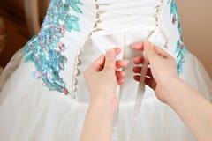 Die Braut wird geholfen, sich das Korsett oben zu schnüren stockbild