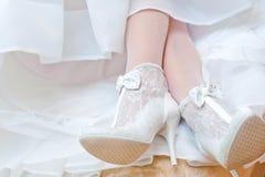 Die Braut zeigt weiße Hochzeitsschuhe Lizenzfreies Stockfoto