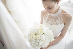 Die Braut, zum auf dem Sofa zu sitzen hat einen Blumenstrauß lizenzfreie stockbilder
