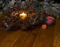 Die brennende Kerze und der Weihnachtskranz Stockfotografie