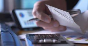 Die Buchhaltergeschäftsperson, die an Steuererklärung arbeitet, bildet sich am Schreibtisch auf Taschenrechner stock video footage