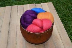 Die bunte Schafwolle, die in einem Kupfer vorspinnt, färbte Glasschüssel Stockfotos