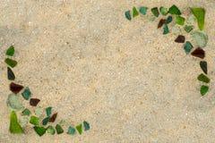 Die bunten Glasstücke, die durch das Meer auf nassem Sand poliert werden, setzen in Form eines Rahmens auf den Strand lizenzfreie stockfotos