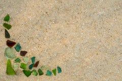 Die bunten Glasstücke, die durch das Meer auf nassem Sand poliert werden, setzen in Form eines Rahmens auf den Strand stockbild