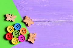 Die bunten hölzernen runden Knöpfe, die in Form einer Blume auf einem Grünbuch ausgebreitet werden, bedecken, hölzerne Schmetterl stockbild