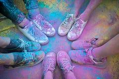Die bunten Schuhe und die Beine von Jugendlichen am Farblaufereignis lizenzfreies stockfoto