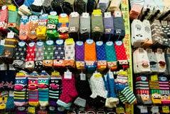Die bunten Socken des Designs, die in Kaufhaus mit großer Auswahl von lustigen Kindern eingestellt werden, tragen Lizenzfreies Stockbild