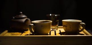 Die chinesische Teekanne des Lehms, zwei Cup und Zucker auf einer hölzernen Tabelle abend Puer Teeschreibtisch cup Stockbild