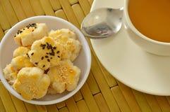 Die chinesischen Miniplätzchen, die Schwarzweiss-indischen Sesam zurechtmachen, essen mit heißem Tee Lizenzfreies Stockfoto