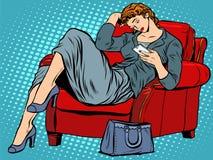 Die Dame im Stuhl schaut Smartphone lizenzfreie abbildung