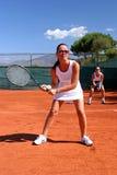 Die Damen, die Service während Doppelte warten, gleichen am Tennis in der heißen Sonne mit blauem Himmel ab Lizenzfreie Stockfotos