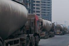 18 die Dec, 2014, Peking, China, Vacuümvrachtwagen op de weg naast de onvolledige gebouwen berijden stock afbeelding