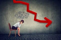 Die deprimierte Geschäftsfrau, die unten dem fallenden Pfeil glaubt verwirrt betrachtet, hat viele Fragen stockbild