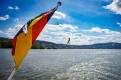 Die deutsche Flagge am Heck eines Schiffs auf dem Rhein mit blauer SK Stockbild