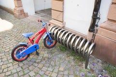 Die deutschen Kinder, die kleines Fahrrad radfahren und Verschluss stoppen, dreht sich am Parken Stockbilder