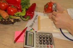 Die Diätetikerernährungswissenschaftlerprüfung überprüfen eine Tomate mit Stethoskop Frau mit Mastungesunder fertigkost lizenzfreies stockfoto