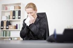 Die Direktorin, die mit Augen niest, schloss in ihrem Büro Stockfotografie