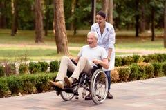 Die Doktorrollen ein älterer Patient auf einem Rollstuhl im Park Sie haben Spaß Lizenzfreies Stockbild