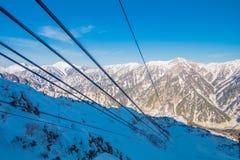 Die Drahtseilbahnlinie von Tateyama Kurobe alpin am Sonnenscheintag mit Hintergrund des blauen Himmels ist eine von den wichtigst stockbilder