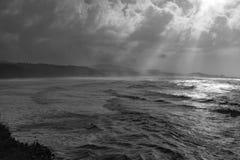 Die drastische und schroffe Orgeon-Küstenlinie mit den Lichtstrahlen, die durch die Brüche in den Wolken kommen lizenzfreie stockfotos
