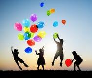 Die draußen spielenden Kinder steigt zusammen im Ballon auf Lizenzfreie Stockbilder