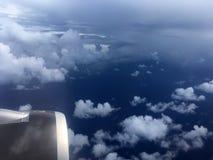 Die Draufsicht von Wolken und von Himmel von einem Flugzeugfenster Stockfoto