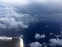 Die Draufsicht von Wolken und von Himmel von einem Flugzeugfenster Lizenzfreie Stockbilder
