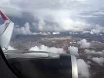 Die Draufsicht von Wolken und von Himmel von einem Flugzeugfenster Lizenzfreie Stockfotos