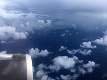 Die Draufsicht von Wolken und von Himmel von einem Flugzeugfenster Stockfotografie